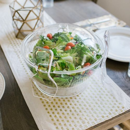 Chilled salad bowl on ice with spoon and fork
