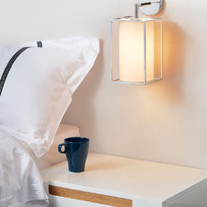 The light of the bedside wall lamp in the bedroom is soft and warm.